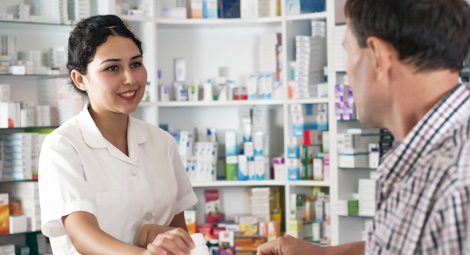 female pharmacist giving a prescription to a customer