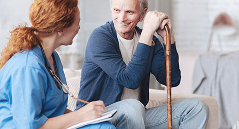 Older gentleman being visited at home by a female doctor